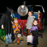 "Photo courtesy B. Duncan who writes, ""My little boy is a Thomas the Train fan so we decided to go with that theme. We created this out of some old plywood and a 55 gallon barrel. We cut a hole for the mouth of Thomas and put our bags of treats in there."""